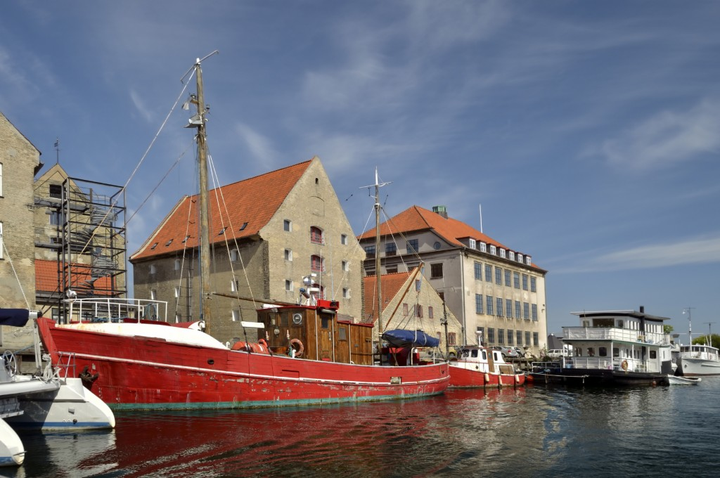 Dockside ships in the Copenhagen canal and red tile roofs provide a very colorful image likely to be seen on a stroll through old town.